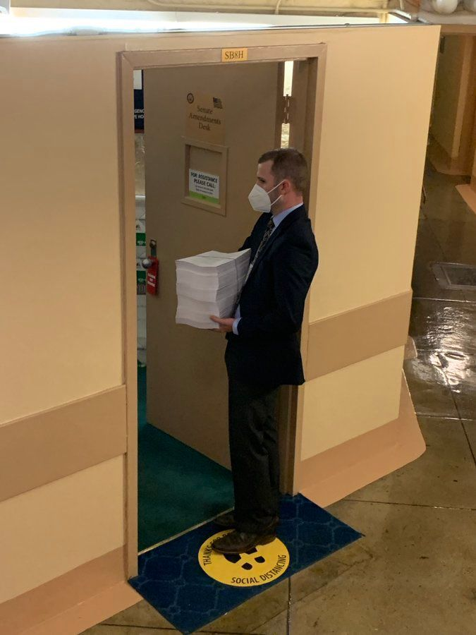 A congressional aid delivers the 2,700 page tome to the office the Senate Amendments Desk.